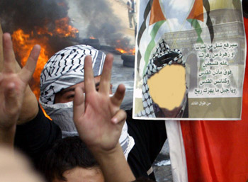 Palestinians flash the victory sign during a rally following the announcement of the death of Palestinian President Yasser Arafat near the West Bank city of Hebron on November 11, 2004. Palestinian leader Yasser Arafat, who rose from guerrilla icon to Nobel peace prizewinner but ended up isolated and locked in conflict with Israel, died in a French hospital. Photo by/Nayef Hashlamoun
